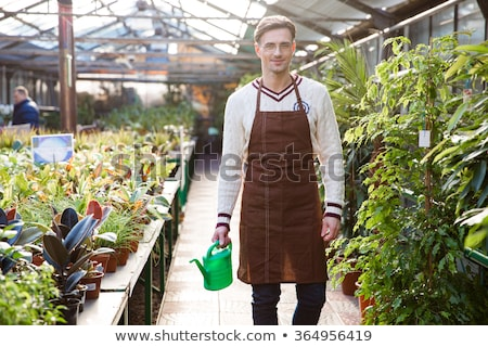 Smiling man gardener standing and holding watering can in orangery Stock photo © deandrobot