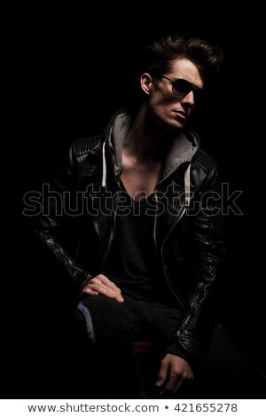 fashionable rocker in black leather jacket posing seated Stock photo © feedough