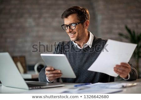 Businessman reading report or document stock photo © lovleah