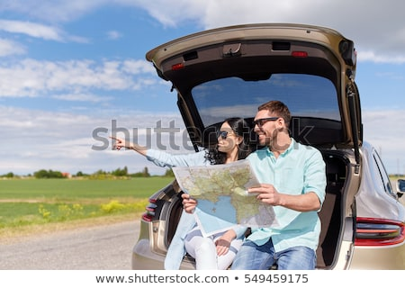 happy young couple sitting in car and pointing finger stock photo © deandrobot