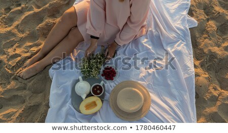 Girl meets the dawn on the beach Stock photo © Kotenko