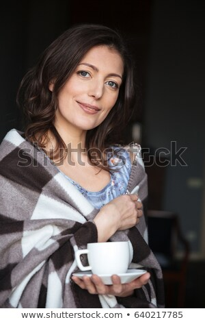 smiling woman in plaid standing indoors while drinking coffee stock photo © deandrobot