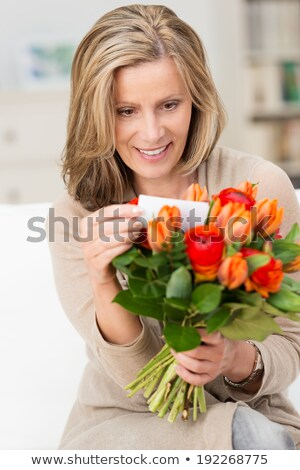 woman holding flowers and reading note smiling stock photo © monkey_business