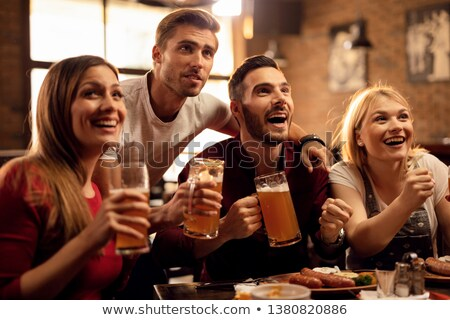 group of friends drinking beer while watching match stock photo © wavebreak_media
