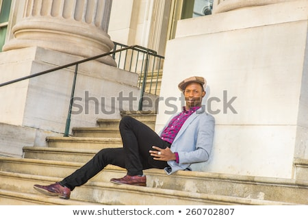 Stylish african man in leather jacket sitting on a stairs Stock photo © deandrobot
