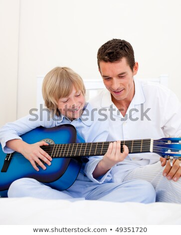 Father and son on bed with guitar Stock photo © IS2
