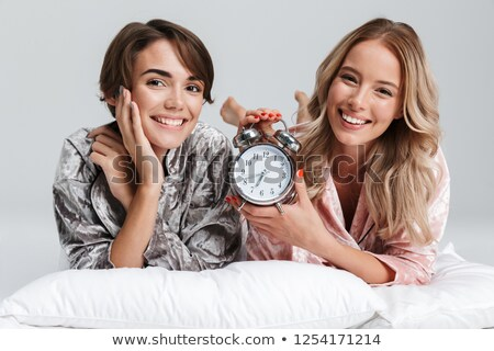 Charming woman posing on bed with clock Stock photo © dash