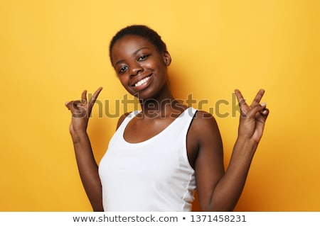 Pretty african woman isolated over yellow background showing okay gesture. Stock photo © deandrobot