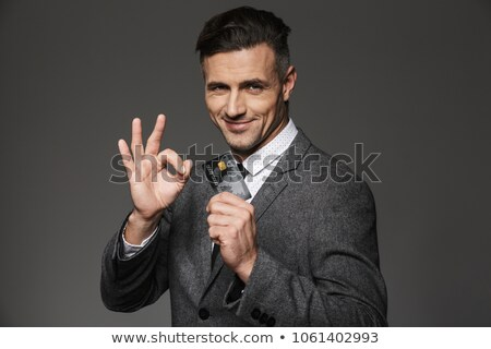 Image of successful businessman 30s in suit holding credit card  Stock photo © deandrobot