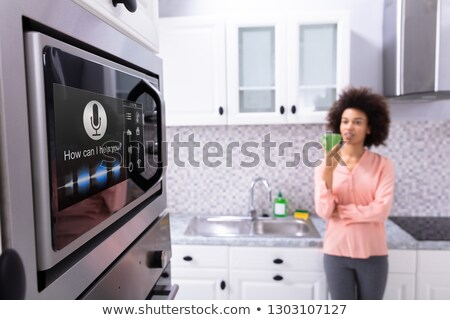 Woman Looking At Oven With Voice Recognition Function Stock photo © AndreyPopov