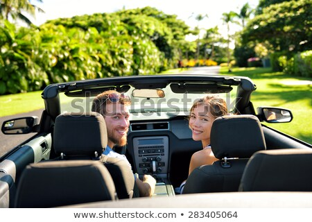 couple driving in convertible car and looking back Stock photo © dolgachov