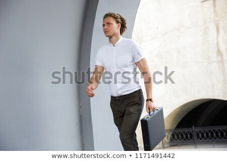 Picture of Calm curly business man with briefcase looking away Stock photo © deandrobot