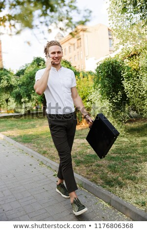 Full length image of Pleased curly business man with briefcase Stock photo © deandrobot