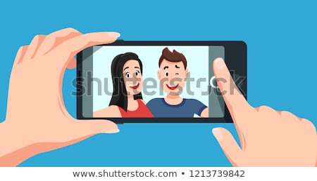 image of young couple using mobile phone and taking selfie photo stock photo © deandrobot