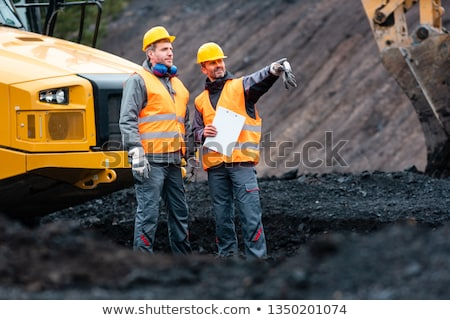 worker with a plan and a clipboard discussing things in quarry stock photo © kzenon