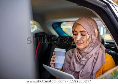Young arabian woman with laptop typing and talking on smartphone in taxi cab Stock photo © pressmaster