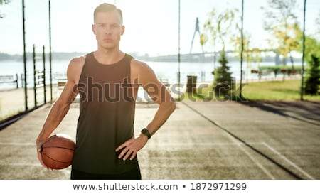 Serious active guy with ball standing on basketball court or playground Stock photo © pressmaster