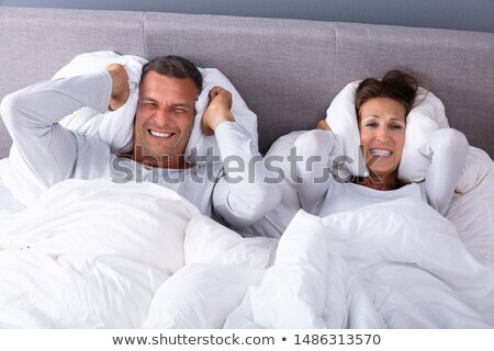 Disturbed Couple Covering Their Ears With Pillow On Bed Stock photo © AndreyPopov