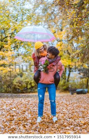 Afroamerikai férfi hordoz kaukázusi lány háton ősz Stock fotó © Kzenon