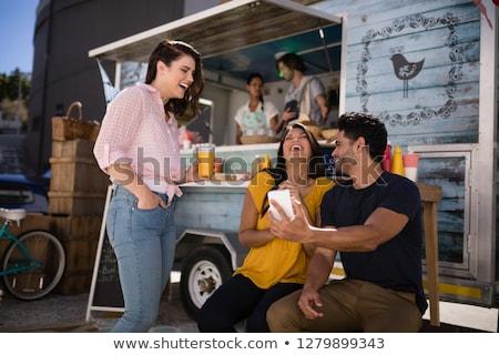 Amis regarder téléphone portable souriant alimentaire camion Photo stock © wavebreak_media