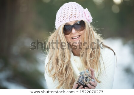Woman holding wrapped gifts tied with string in snow landscape Stock photo © lovleah