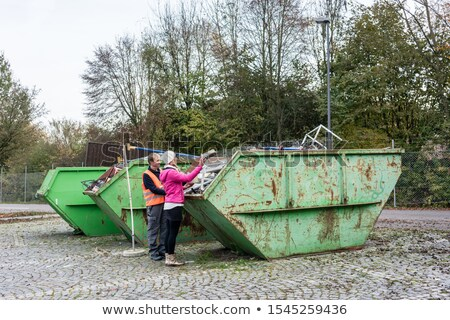 Woman putting scrap metal in container to be recycled Stock photo © Kzenon