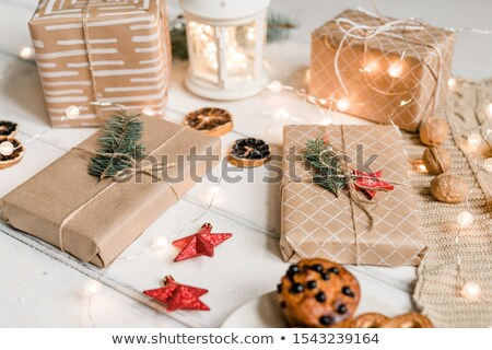Packed gifts among decorative red stars, walnuts, sparkling garlands on table Stock photo © pressmaster
