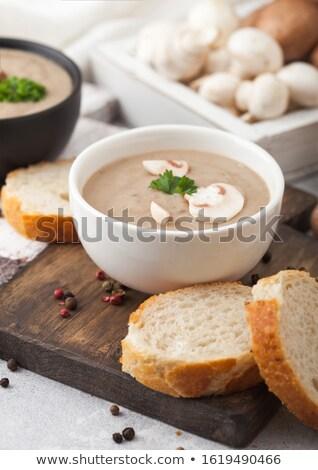 Ceramic bowl plates of creamy chestnut champignon mushroom soup with spoon, pepper and kitchen cloth Stock photo © DenisMArt