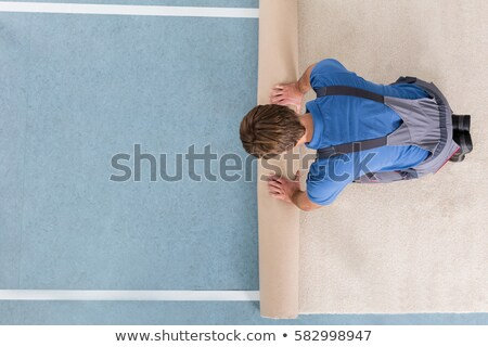 Worker In Overalls Unrolling Carpet Stock photo © AndreyPopov