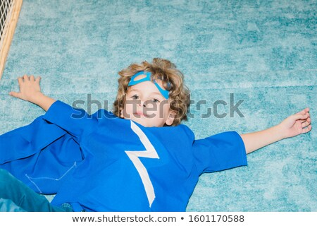 Adorable little boy in blue mantle and t-shirt lying on soft floor on play area Stock photo © pressmaster