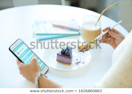 Hands of young female scrolling in smartphone and eating appetizing cake Stock photo © pressmaster