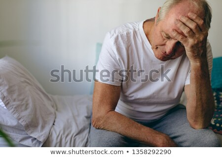 Front view of frustrated senior Caucasian  male patient sitting on bed at retirement home. He touche Stock photo © wavebreak_media