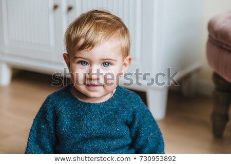 Close up portrait of blonde little child with plump cheeks, looks with blue eyes into camera, has in Stock photo © vkstudio
