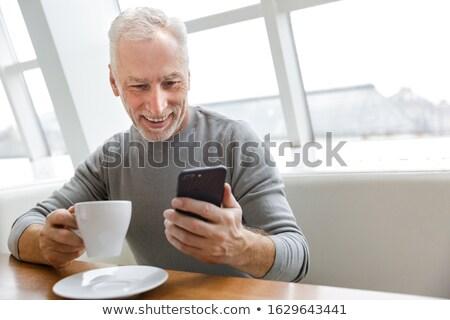 Fotografia radosny dojrzały mężczyzna pitnej kawy smartphone Zdjęcia stock © deandrobot