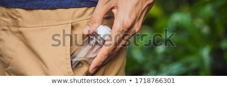 man put a hand sanitizer gel into his trouser pocket when he is going to go outside during corovid - Stock photo © galitskaya