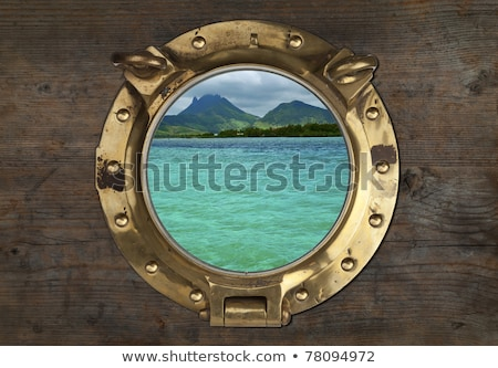 Antique Porthole with Tropical View on a wooden Wall Background. Stock photo © premiere