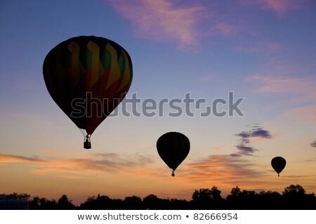 Hot-air balloon floating against a reddish dawn sky Stock photo © Balefire9