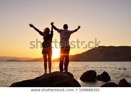 Stock fotó: A Girl With A Guy Raised His Hands To The Sun