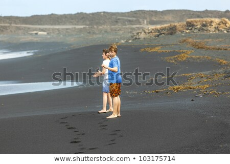 boy has fun in the spume at the black volcanic beach Stock photo © meinzahn