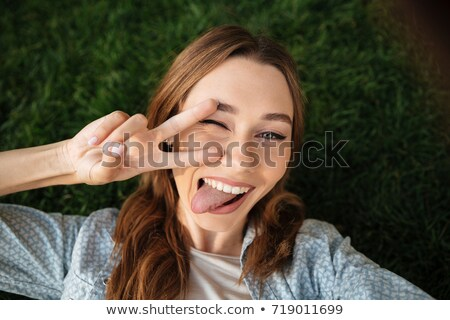 szórakoztató · aranyos · fiatal · nő · mutat · nyelv · készít - stock fotó © deandrobot