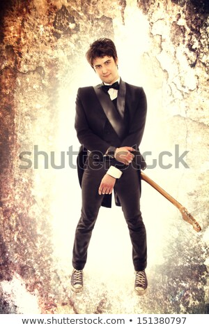 attractive charismatic male guitarist standing and playing electric guitar stock photo © deandrobot