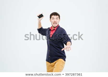 angry man throwing phone into camera stock photo © deandrobot