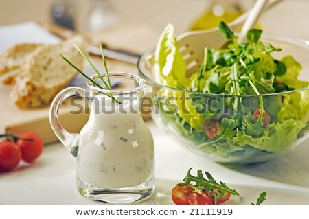 Bowl of greens and a jug of salad dressing Stock photo © Digifoodstock