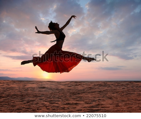 graceful young woman dancer dancing on the beach stock photo © deandrobot