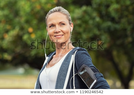 Happy fitness woman with armband standing and listening to music Stock photo © deandrobot