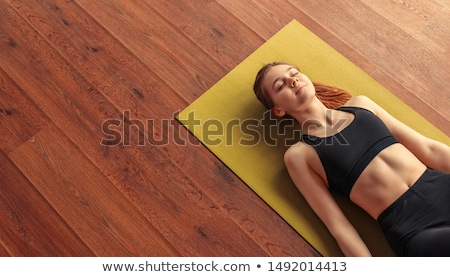 Smiling relaxed woman lying with eyes closed on the floor Stock photo © deandrobot