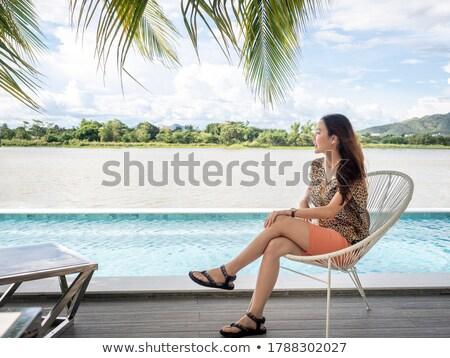Nő ül perem végtelen medence hotel Stock fotó © Kzenon