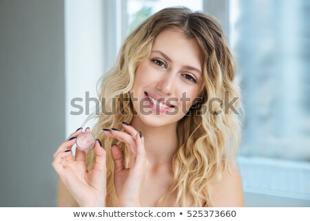 Blond woman using moisturizer. Stock photo © lithian