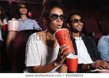Serious young friends sitting in cinema watch film Stock photo © deandrobot