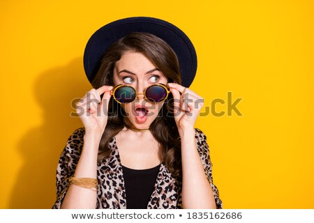 Shocked young girl in hat looking up at copyspace Stock photo © deandrobot